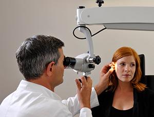 Ihr HNO-Arzt untersucht die Ohren mit einem Ohrmikroskop und einem Ohrtrichter